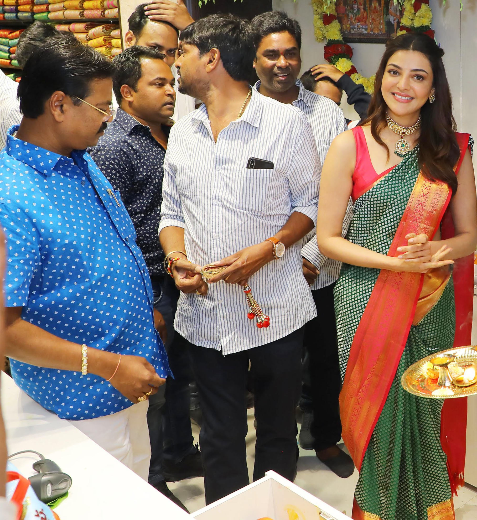 Star Actress Kajal Agarwal, at the inauguration of the 5th Maangalya Shopping Mall in Hyderabad at Chintal, today, as Mr Kasam Namashivaya (extreme left), Chairman, Maangalya Shopping Mall; looks on.