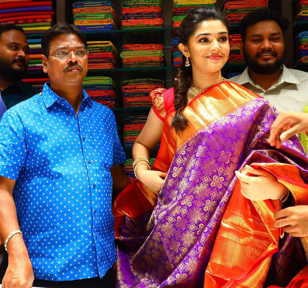 Actress Krithi Shetty looking at a saree after inaugurating the 10th Maangalya Shopping Mall in Hyderabad, at AS Rao Nagar